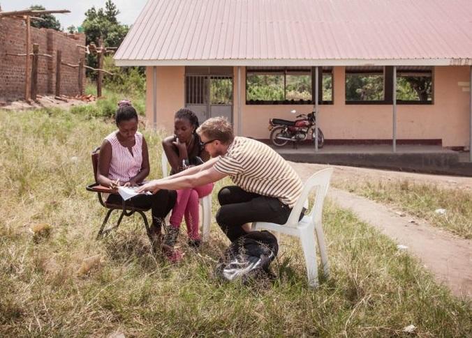 Kolme ihmistä istuu ulkona keskustelemassa vihossa lukevista asioista