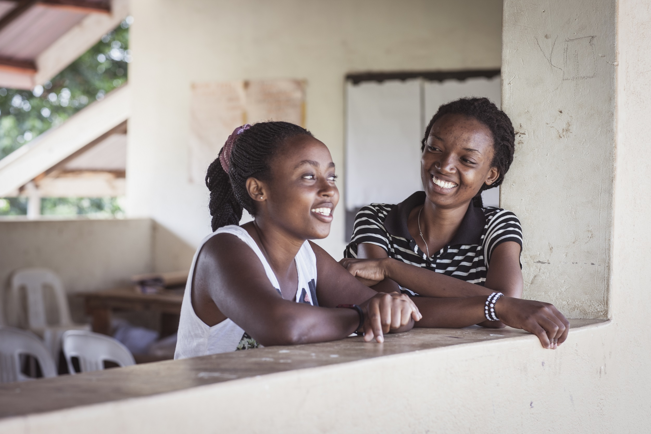 Kaksi naista nojaa ikkunanpuitteeseen ja nauraa
