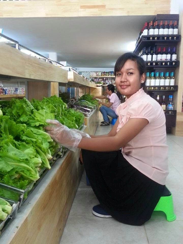 Kaupan työntekijä hymyilee hyllyttäessään vihreitä salaatinlehtiä